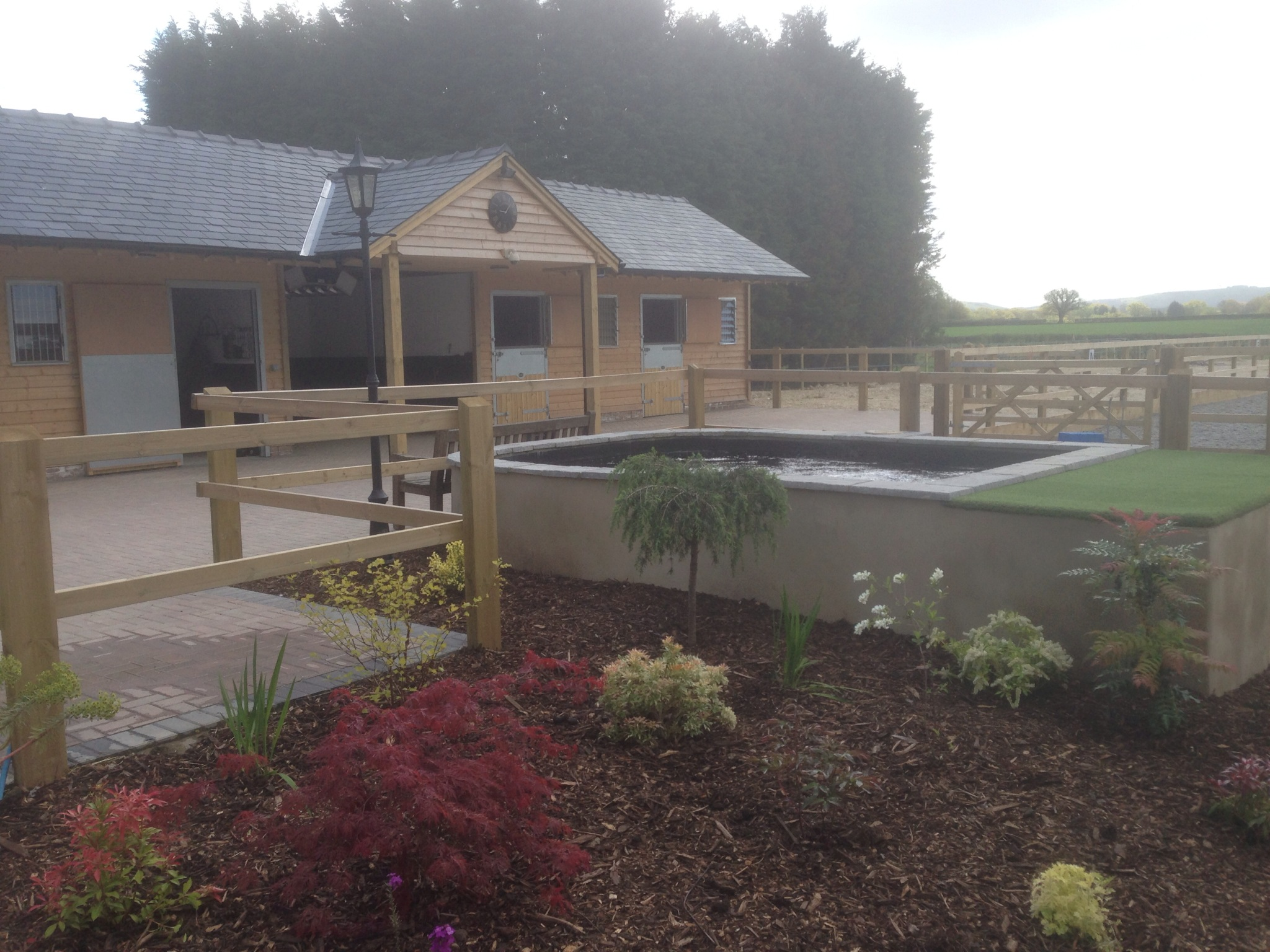 A newly built timber stables with block-paved yard in front and grass and gardens laid