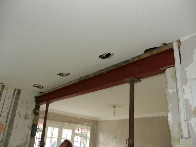The fitting of a new steel lintel between two rooms